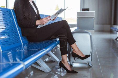 jeune femme lisant le journal à la salle d'embarquement à l'aéroport