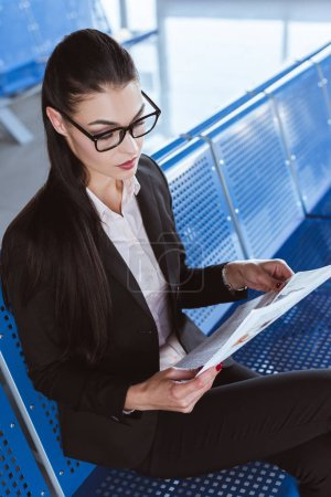Photo for Young beautiful businesswoman in glasses reading newspaper at departure lounge in airport - Royalty Free Image