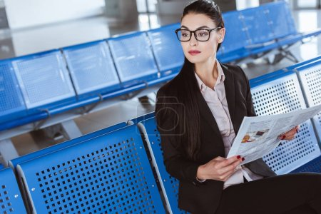 young beautiful businesswoman in glasses reading newspaper at departure lounge in airport