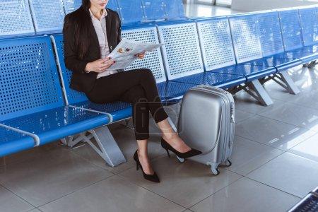 jeune femme d'affaires assis devant la salle d'embarquement à l'aéroport et de lecture de journal