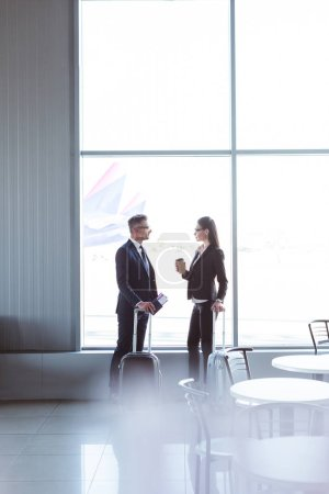 businessman and businesswoman standing and talking at departure lounge in airport