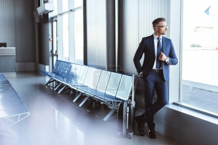Photo for Handsome businessman standing at departure lounge and looking at window in airport - Royalty Free Image