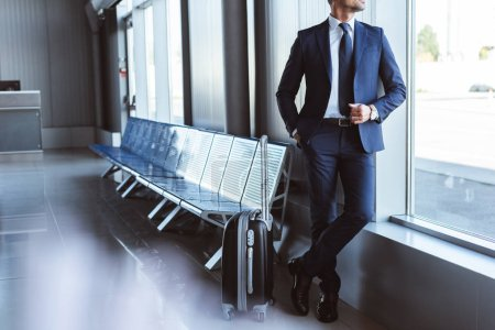 businessman standing at departure lounge and looking at window in airport