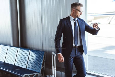 businessman standing at departure lounge near window and looking at watch in airport
