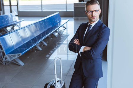 businessman in glasses standing with luggage at departure lounge in airport