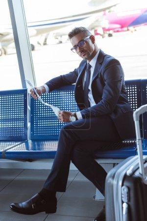 bel homme assis près de fenêtre à la salle d'embarquement et de lecture de journal