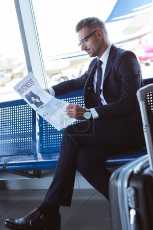 Photo for Handsome businessman sitting near window at departure lounge and reading newspaper - Royalty Free Image