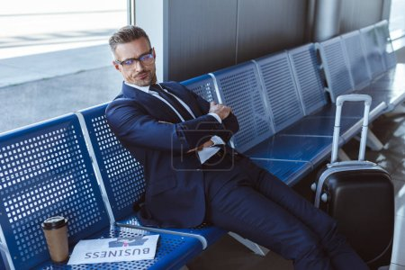 Photo for Businessman in glasses sitting near window with newspaper and paper cup at departure lounge - Royalty Free Image