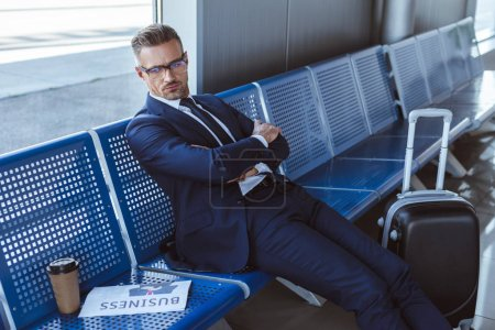 tired businessman in glasses sitting near window with newspaper and paper cup in airport