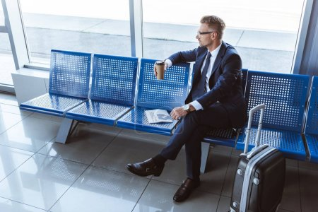 businessman in glasses sitting with newspaper and coffee to go in airport