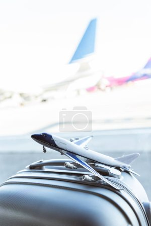 close up of small plane model on grey suitcase in airport