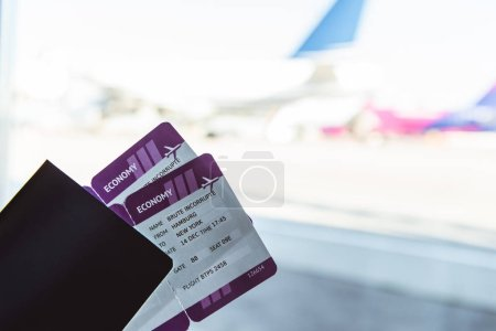 close up of air tickets and travel bag in airport