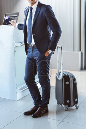 handsome businessman with suitcase standing near check-in desk in airport