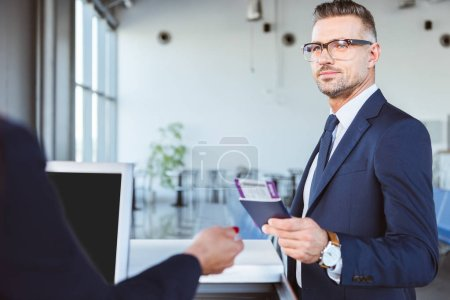businessman with documents at check-in in airport