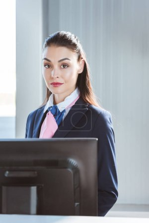 adult female airport worker standing at check-in desk