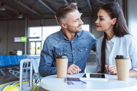 Photo pour Adulte couple assis dans l'aéroport et en regardant l'autre - image libre de droit
