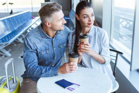 Foto de Pareja adulta con café para ir a buscar en la ventana en la sala de embarque en aeropuerto - Imagen libre de derechos