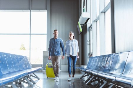 Romantic couple holding hands walking with yellow baggage in the airport