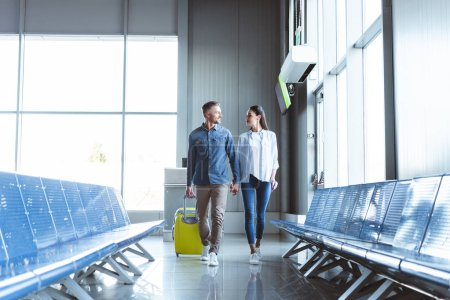 Man and woman walking with yellow travel bag in the airport