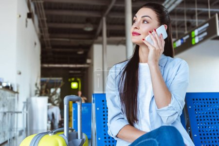 Photo for Stylish woman talking on smartphone and sitting in the airport with yellow suitcase - Royalty Free Image