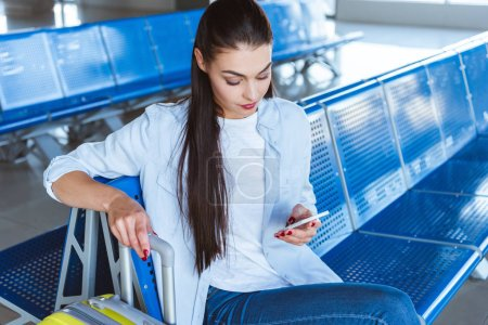 Woman sitting in the airport and checking her smartphone