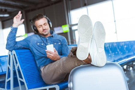 Man enjoying the music and relaxing waiting for his flight in the airport