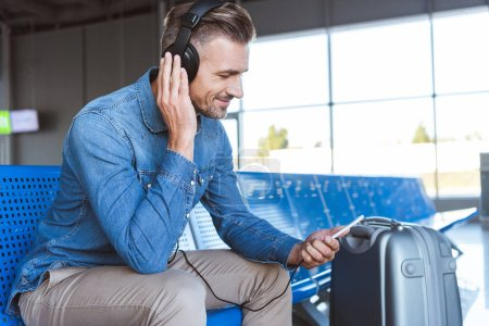 Photo for Handsome man sitting and enjoying music in the airport - Royalty Free Image