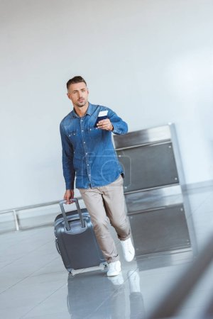 Photo for Handsome tourist with silver travel bag in the airport - Royalty Free Image