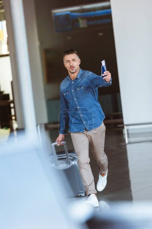 Photo for Man walking in the airport and pointing something with the passport in his hand - Royalty Free Image