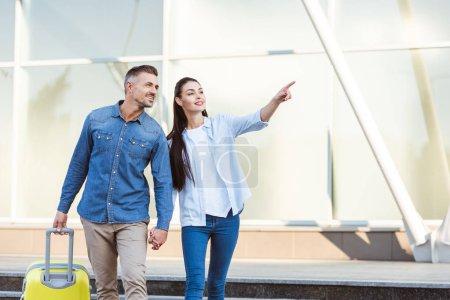 Photo pour Un couple de touristes à la recherche de suite, souriant et pointant à quelque chose - image libre de droit