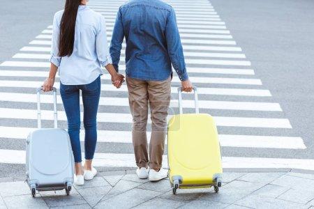 Photo pour Une vue recadrée d'un couple de voyageurs de passage pour piétons, tenant les mains et tirant leurs bagages - image libre de droit