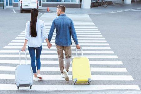 Photo pour Un couple de touristes de passage pour piétons, tenant les mains et en tirant leurs bagages - image libre de droit