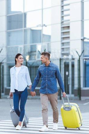 Photo pour Un couple de touristes de passage pour piétons, tenant les mains, en regardant l'autre et tirant leurs bagages - image libre de droit