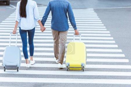 Foto de Un par de turistas cruce peatonales, sosteniendo las manos y tirando de su equipaje - Imagen libre de derechos