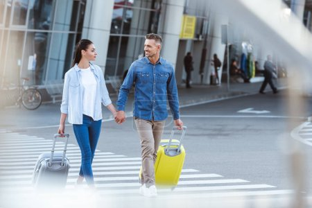 A couple of tourists crossing pedestrian with luggage while holding hands and looking at each other