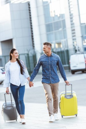 Foto de Un par de turistas cogidos de la mano, tirando de su equipaje, mirando el uno al otro y sonriendo en el fondo del aeropuerto - Imagen libre de derechos