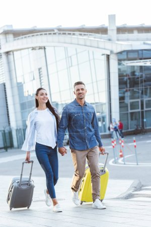 Photo for Happy couple of tourists crossing pedestrian, holding hands and pulling their luggage - Royalty Free Image