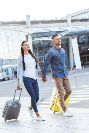 A couple of tourists crossing pedestrian, holding hands and pulling their travel bags
