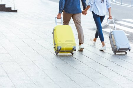 cropped view of couple of tourists holding hands and pulling their luggage