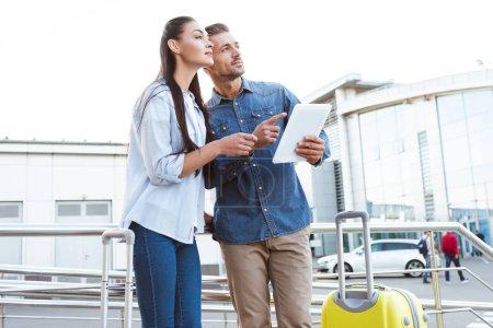 Foto de Pareja de turistas con equipaje con tableta digital, apuntando y mirando lejos - Imagen libre de derechos