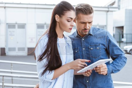 couple attentively looking into digital tablet, woman pointing at screen