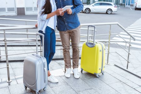 Cropped view of couple of travelers with luggage using digital tablet