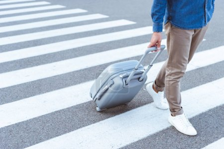 Photo for Cropped view of a tourist in white shoes with grey travel bag - Royalty Free Image