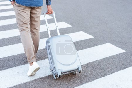 Cropped view of a tourist in white shoes pulling his luggage