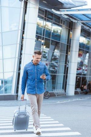 Photo pour Bel homme adulte avec des bagages, passage piéton, regardant dans smartphone sur le fond de l'aéroport - image libre de droit