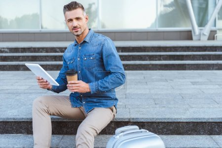 Photo pour Bel homme adulte avec une tasse de café, assis sur l'escalier, tenant la tablette numérique et souriant à la caméra - image libre de droit