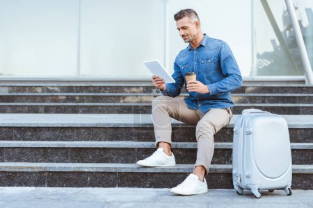 Handsome adult man with a coffee to go sitting on the staircase with luggage and using digital tablet