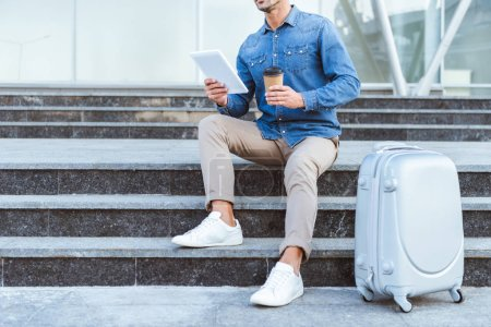 Man sitting on the staircase with luggage, holding digital tablet and coffee to go