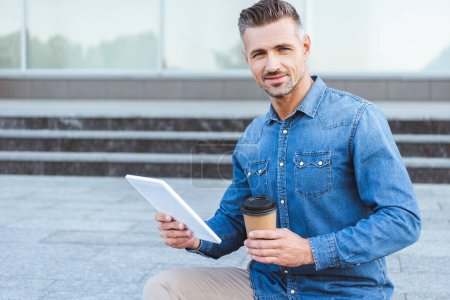 Photo pour Bel homme adulte avec une tasse de café, tenant la tablette numérique, regardant la caméra et assis sur l'escalier - image libre de droit
