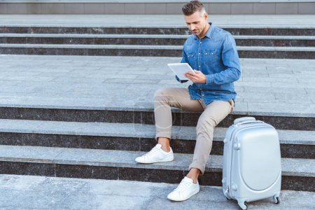Photo pour Bel homme adulte assis sur l'escalier avec bagages et à l'aide de tablette numérique - image libre de droit